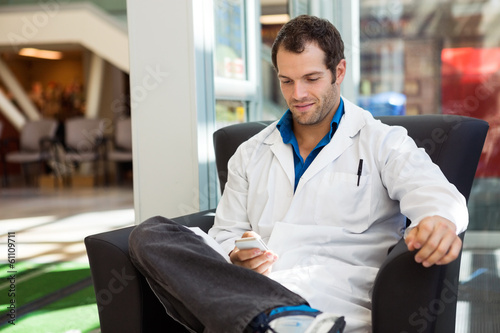 Doctor Using Mobile Phone On Chair