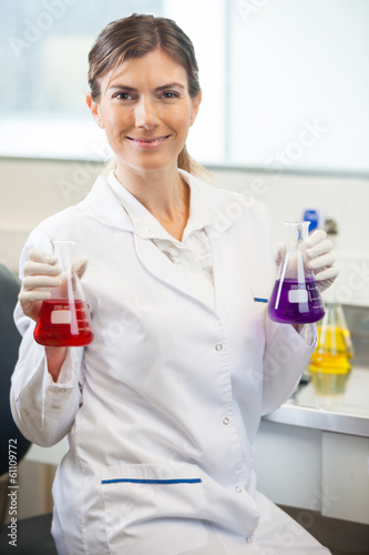 Scientist Examining Flasks With Different Chemicals