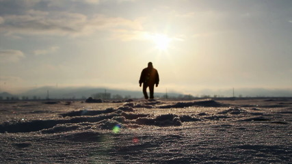 Silhouette of a man walking in deep snow at sunset