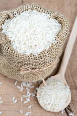 rice in a burlap bag on wooden surface