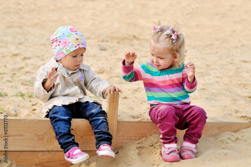 toddlers girls playing in sand