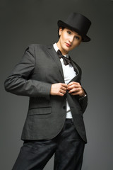 Young woman wearing man's suit posing over grey background