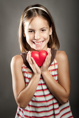little girl holding red heart