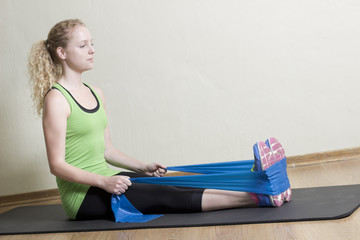Young Female Pilates Instructor using Rubber band