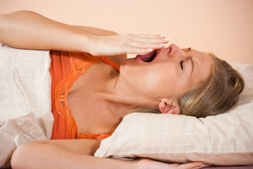 Young woman lying in bed and yawning