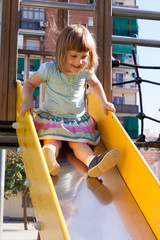baby girl   on slide at playground area