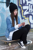 Trendy teenager with smartphone and skateboard