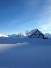 baita innevata e lago ghiacciato e cielo