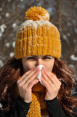 Woman sneezing into tissue, winter outdoor portrait