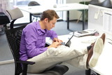 businessman in office working with tablet - bad sitting posture