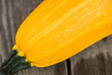 Yellow zucchini on the wooden floor, close-up