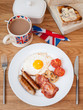 cooked english breakfast on a wooden table top