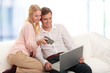 Happy young couple using laptop in living room