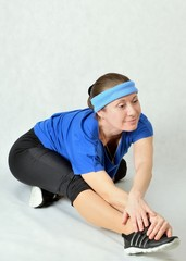Fitness woman doing exercises, stretching the leg muscles