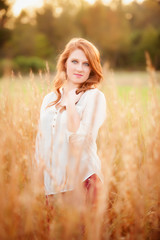 red haired girl in a field
