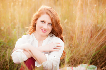 red haired girl in a field smiling