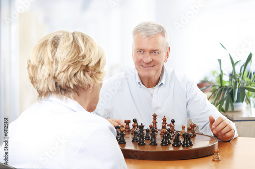 Couple playing chess in living room