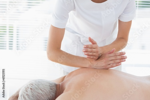 Physiotherapist massaging back of man