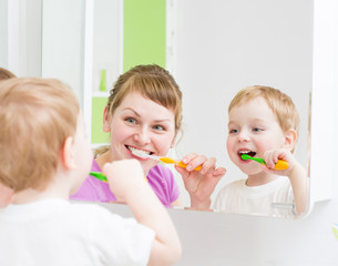 Happy mother and child teeth brushing  in bathroom front of mirr