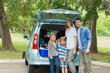 Family of four by car trunk while on picnic