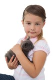 Cute girl holding grey kitten smiling at camera