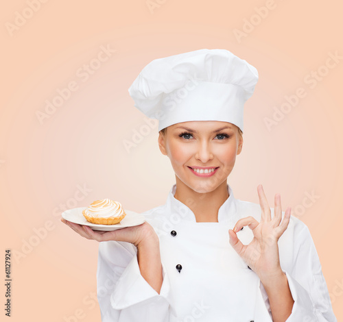 smiling female chef with cake on plate