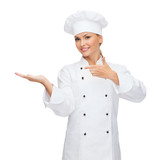 smiling female chef holding something on hand
