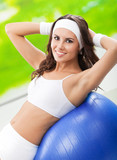 Woman exercising with fitball, outdoors