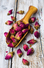 wooden scoop with tea buds of roses