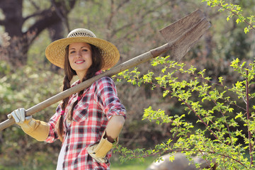 Beautiful and smiling girl  posing with a shovel