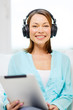 smiling woman with tablet pc and headphones
