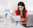Frau hat Stress im Job - sitzend im Büro und frustriert