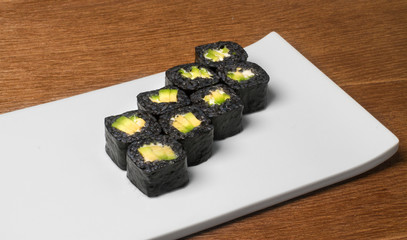 Image of black sushi with avokado on plate in restaurant