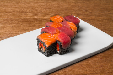 Image of black sushi with salmon on plate in restaurant