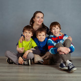 Portrait of happy mother and three sons, studio