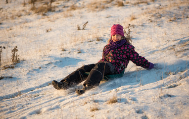 Girl sledding in the light of sunset