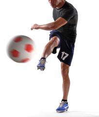 Jugador de fútbol pateando balón.