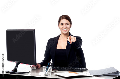 Businesswoman pointing at the viewer in her office