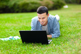 Student using a laptop on the grass