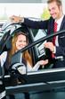 Verkäufer und Kundin mit Auto im Autohaus