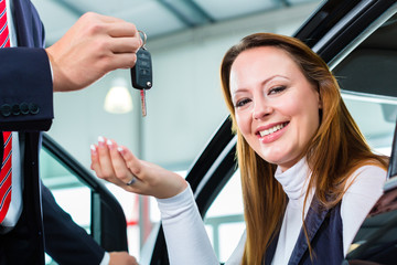 Dealer, female client and auto in car dealership