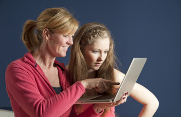 Adult and teenager looking at a laptop computer