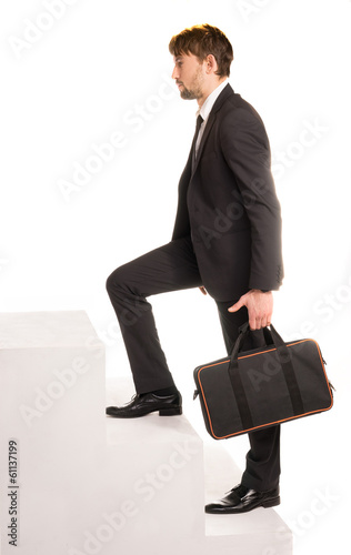 Businessman climbing stairs with a briefcase