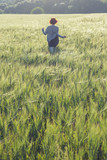girl running across green field in the morning