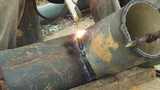 Welder uses arc welding pipe metal on site.