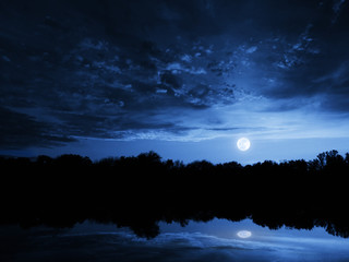 Dramatic Moonrise With Deep Blue Sky Lake Reflections and Clouds