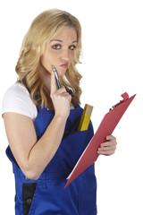 Junge Handwerkerin mit Blaumann beim Überlegen