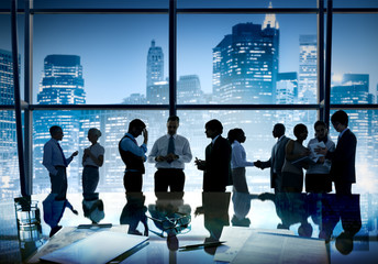 Group of business people discussing at city view reflected onto