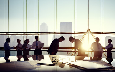 Group of business people and men bowing reflected onto table wit