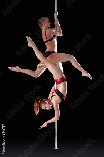 Two athletic young girls dancing on pilon